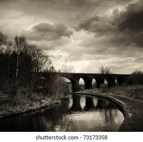 Black and white photo of an arc bridge with dramatic sky in Huddersfield.
