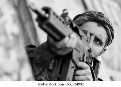Black and white photo of armed & dangerous soldier shooting with automatic rifle.Terrorist military man in combat ammunition targeting with rifle gun.Guerrilla soldier ready to fight