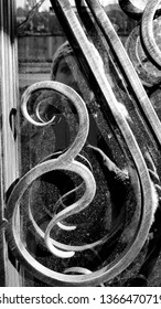 Black and white photo of art deco style volute on vintage door with blurred selfie in dusty mirror glass. Woman fuzzy portrait through ornate gratings of retro door. Reflection in dirty glass surface