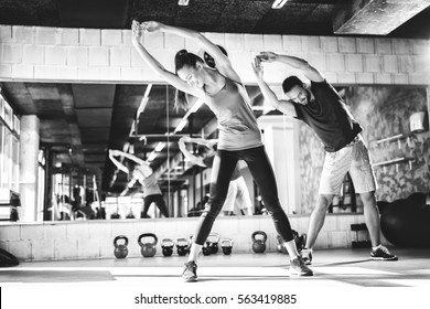 Black and white photo of attractive athletes doing stretching exercises at the gym.