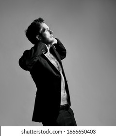 black and white photo of awesome male with cool hairstyle, in black classic suit on naked body. He opened his jacket and posing sideways against gray studio background. Fashion and beauty concept.