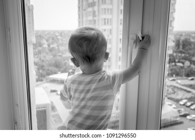 Black and white photo of baby pulling window handle and trying to open it
