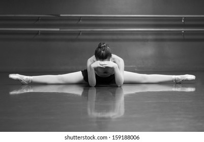 Black & White photo of a ballerina stretching her middle splits, in the studio with barre background.