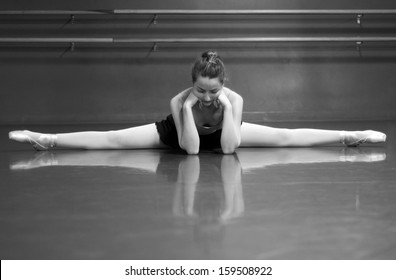 Black & White photo of a ballerina stretching her middle splits, in the studio with barre background