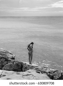 Black and white photo of beautiful girl standing on the edge of rock and looking into the sea