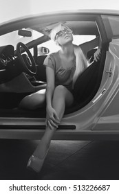Black and white photo. Beautiful sexy fashion woman model with bright makeup sitting in a car. Sexy girl. Blonde. Beauty girl with attractive body in lace lingerie. Supercar. Car