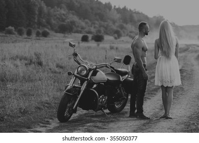 Black and white photo biker couple on a motorcycle in the field. Transferred passionate love photography. Beautiful and motorcycle accessories. Photo for motorcycle