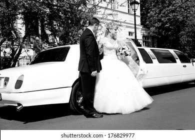 Black and white photo of bride and groom standing near long white limousine