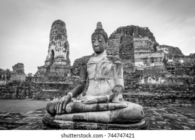 Black and white photo of Buddha statue in Ayuthaya ruined temple in Thailand.
