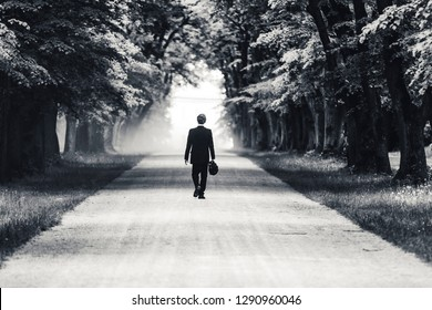 Black and white photo of a businessman or gentleman in a suit walking away on a dusty gravel road. Business man walking in an alley. Old trees and mysterious leaving of a man in a suit.