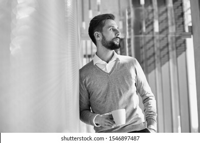 Black and white photo of businessman leaning on wall while drinking coffee or tea in office