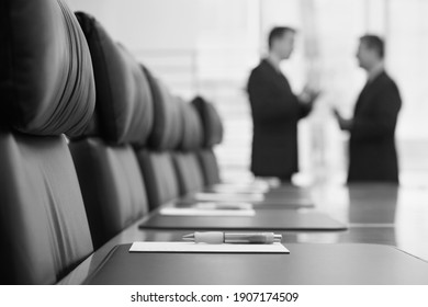 Black and white photo of businessmen talking in conference room