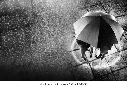 Black and white photo of  businesspeople sheltering under one umbrella