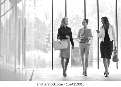 Black and white photo of businesswomen walking while talking in office hall