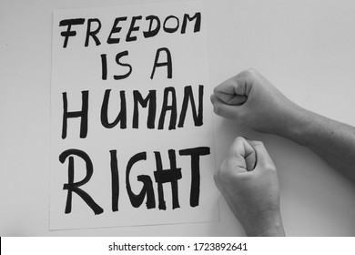 Black and white photo of caucasian woman hitting table with fists next to protest poster with words 'Freedom is a Human Right'. Anti lockdown. Coronavirus COVID-19 protest banner.