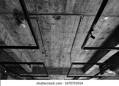 The black and white photo of the cement ceiling and pipes with industrial style.