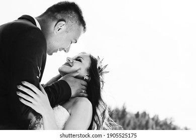 Black and white photo of cheerful emotional newlyweds who hug each other