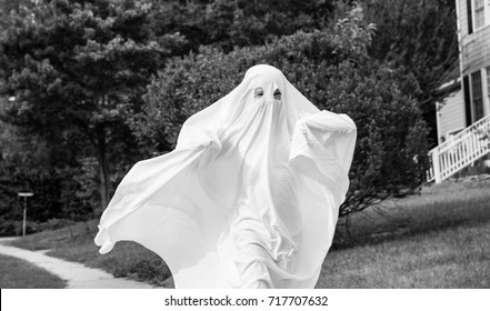 A black and white photo of a child running down the side walk in a ghost costume.