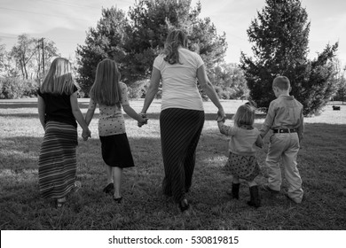 Black and white photo of Christian family, mother, four children walking from behind at park, skirts and dresses, single mom