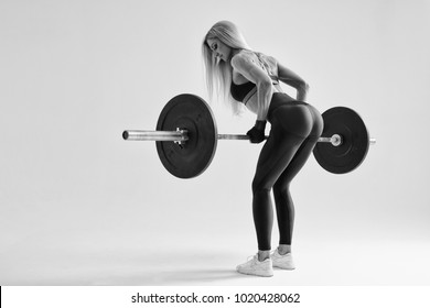 Black and white photo of confident young woman doing weight lifting workout at gym turning back Attractive young woman bodybuilder lifting barbells looking focused