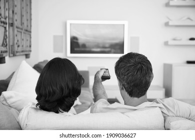 Black and white photo of couple watching television on lockdown