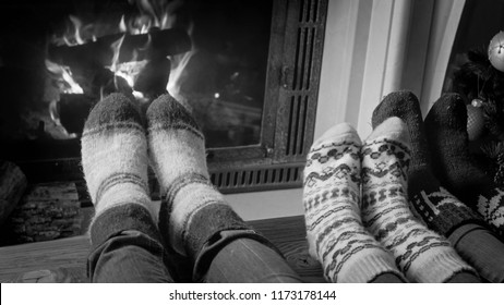 Black and white photo of couple in woolen knitted socks relaxing by the fireside at home