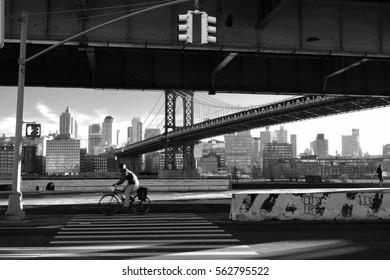Black and white photo of a cyclist riding past the Manhattan bridge New York, Manhattan, United States