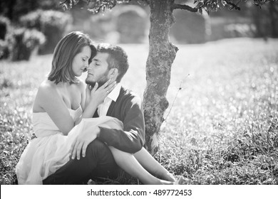Black and white photo of daydreaming wedding couple resting on the lawn