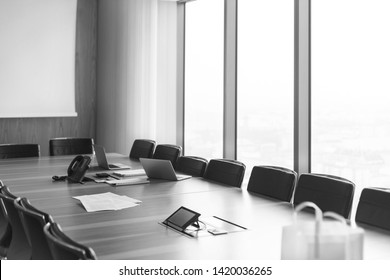 Black and White photo of Documents with laptop and telephone on conference table in boardroom at modern office