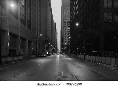 A black and white photo of downtown Chicago. The shot is taken from the middle of the street.