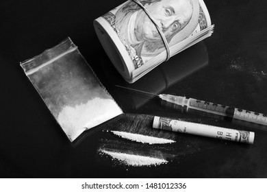 Black and white photo of drug taker`s table with cocaine plastic bag, syringe with some other liquid drugs and pack of dollars on black table. Taking drugs