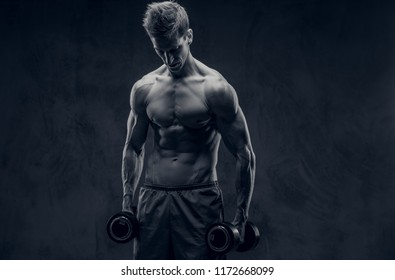 Black and white photo of ectomorph bodybuilder posing with dumbbells and looks down.