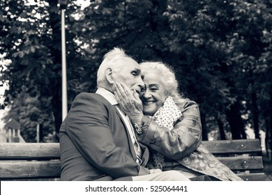 Black and white photo. Elderly family couple talking on a bench in a city park. Happy seniors dating