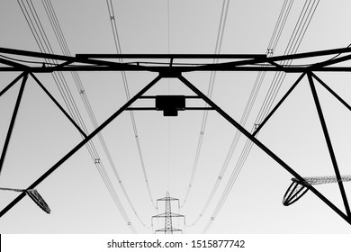 Black and white photo of electricity pylons and electricity cables silhouetted against the cloudless sky with leading lines