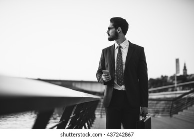 Black and white photo of an elegant businessman holding a mobile phone.