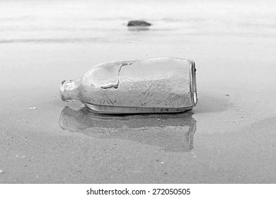 A black and white photo of an empty bottle on a sand beach can be used for back ground