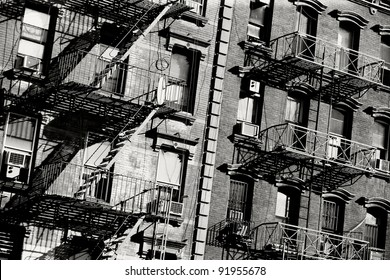 Black and white photo of the exterior of a building in New York with old fire escape.