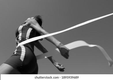 Schwarz-Weiß-Foto von weiblichen Athleten Kreuzung Ziellinie (Bewegungsunschärfe)