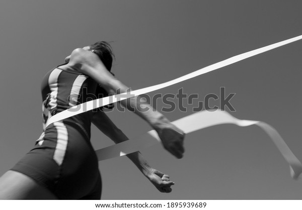 Black and white photo of female athlete crossing finish line(Motion blurr)