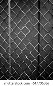 Black and white photo of fence with knitted wire