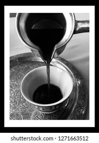 Black and white photo frame of pouring Lebanese arabic coffee in a small cup on a silver plate. Artistic fine art black and white photography