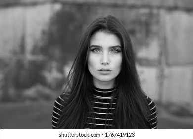 Black and white photo. Frontal portrait of a beautiful girl with straight brunette hair and makeup, looking confident at camera, over black old wall background.