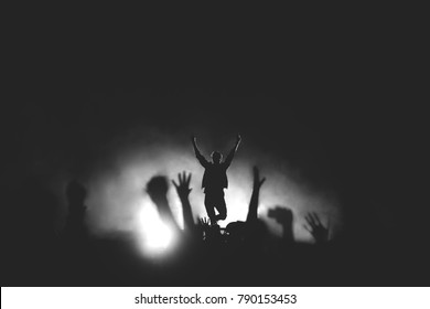 Black and white photo of frontman in a stage backlights with hands raised up to the crowd