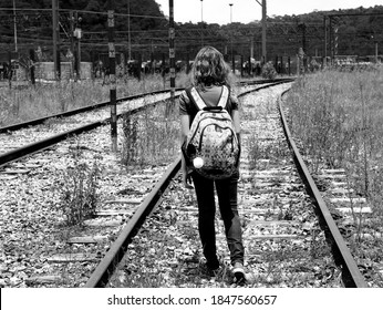 Black and white photo of a girl with a backpack on her back walking on the abandoned train track