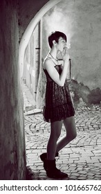black and white photo of girl smoking in the street