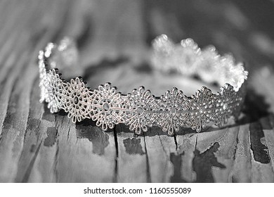 Black and White Photo of a Golden Antique Bracelet Cuff Sticking Out on a Wooden Plank- the Juxtaposition of Luxury among Nature