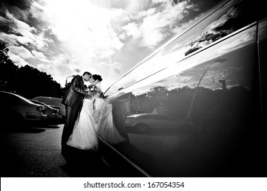 Black and white photo of groom and bride kissing near limousine