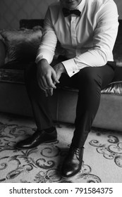 black and white photo: the groom is sitting on the couch and getting ready for the wedding day