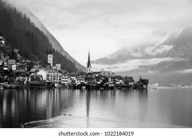 Black and white photo of Hallstatt with lake in foreground