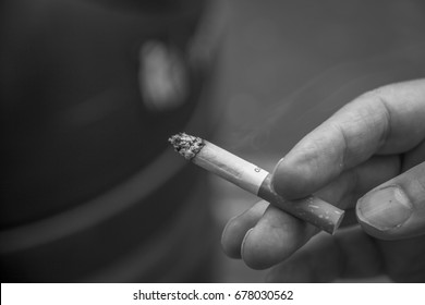 Black and white photo of hand holding cigarette.